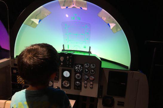 小型ジェット機シミュレーターを操作する5歳児